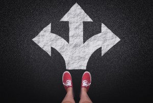 At a crossroads - Decisions and choices concept with large arrow